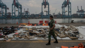 An Indonesian soldiers walk past debris retrieved from the waters where Lion Air flight JT 610 is believed to have crashed at Tanjung Priok Port in Jakarta, Indonesia, Wednesday, Oct. 31, 2018. (AP Photo/Fauzy Chaniago)