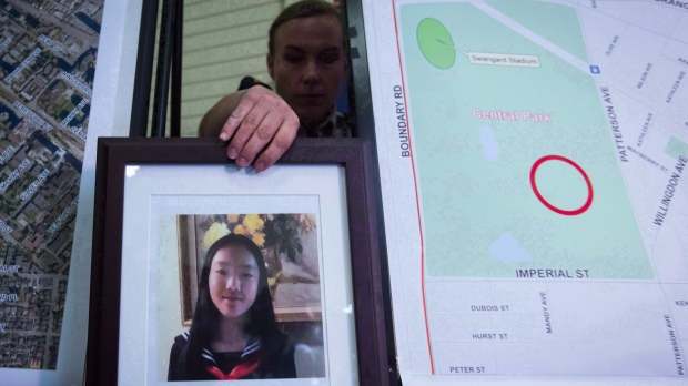 RCMP Cpl. Daniela Panesar places a photo of Marrisa Shen, 13, next to a map indicating where her body was found in Central Park, during a news conference in Burnaby, B.C., on July 19, 2017. THE CANADIAN PRESS/Darryl Dyck