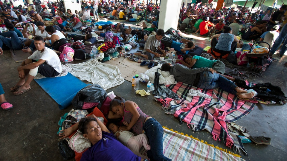 People rest on the ground in a municipal lot serving as a makeshift campground, as a thousands-strong caravan of Central Americans hoping to reach the U.S. border takes a rest day in Juchitan, Oaxaca state, Mexico, Wednesday, Oct. 31, 2018. (AP Photo/Rebecca Blackwell)