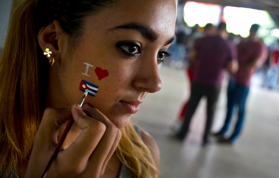 A man paints a Cuban flag on the face of a young student during an event against U.S. trade embargo against Cuba in Havana, Cuba, Wednesday, Oct. 31, 2018. The United Nations will vote Thursday Nov. 1 on a resolution regarding the ongoing U.S. trade embargo against Cuba. (AP Photo/Ramon Espinosa)