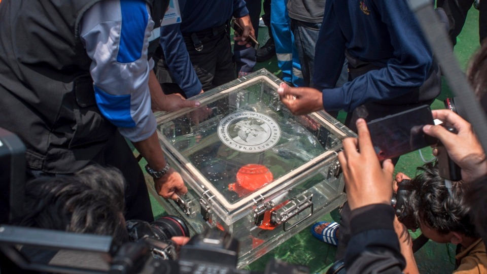 Members of National Transportation Safety Committee lift a box containing the flight data recorder from the crashed Lion Air jet onboard a rescue ship anchored in the waters of Tanjung Karawang, Indonesia, Thursday, Nov. 1, 2018. (AP Photo/Fauzy Chaniago)