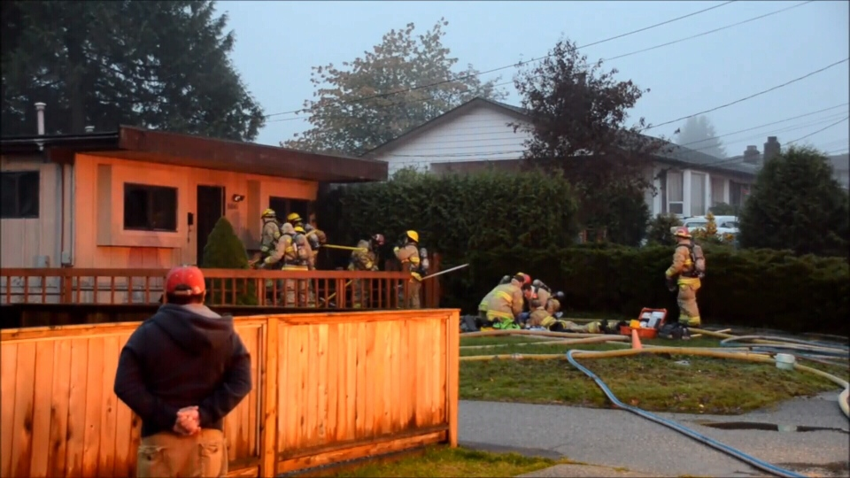 Firefighters perform first aid on a man who was found unconscious inside a burning home in Burnaby Wednesday.
