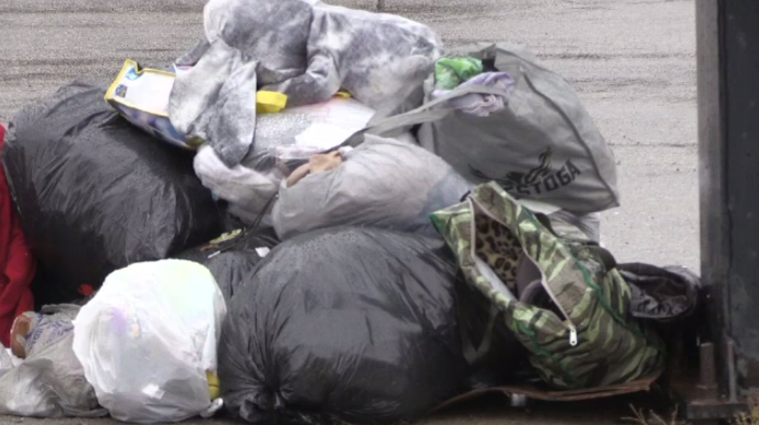 Bags of clothing left on the ground where a body was found in a clothing donation bin.