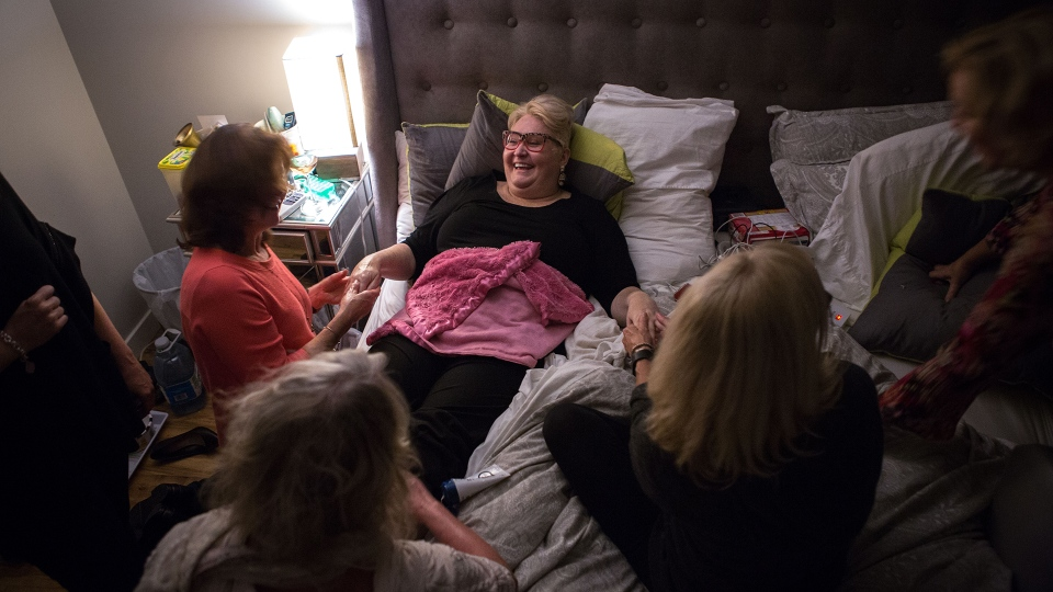 Audrey Parker in bed at her Halifax home, surrounded by friends, on Friday, Oct. 26, 2018. (Chris Donovan)