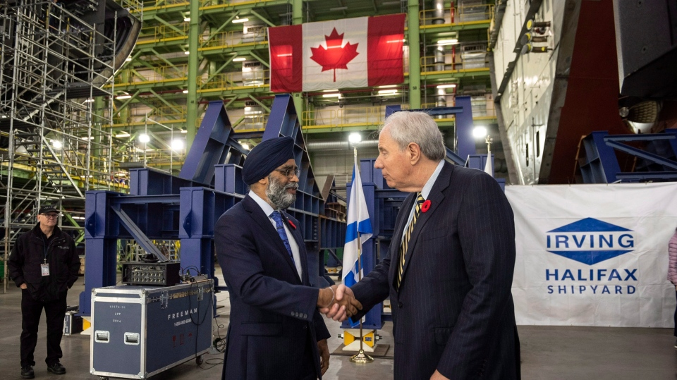 Minister of National Defence Harjit Sajjan, left, shakes hands with Jim Irving, co-CEO of Irving Shipbuilding Inc., following the announcement that the Royal Canadian Navy will receive a sixth Arctic and offshore patrol ship at the Irving shipyards in Halifax on Friday, Nov. 2, 2018. (THE CANADIAN PRESS/Darren Calabrese)