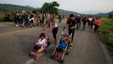 Migrants push strollers carrying young children