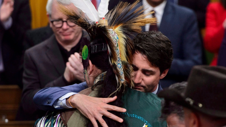 Prime Minister Justin Trudeau hugs a drummer following a performance after delivering a statement of exoneration on behalf of the Government of Canada to the Tsilhqot'in Nation and the descendants of six Tsilhqot'in Chiefs in the House of Commons on Parliament Hill in Ottawa on Monday, March 26, 2018. THE CANADIAN PRESS/Sean Kilpatrick