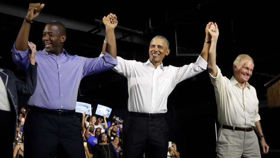 Former President Barack Obama, centre, raises arms with Democratic gubernatorial candidate Andrew Gillum, left, and U.S. Sen. Bill Nelson, D-Fla., right, during a campaign rally, Friday, Nov. 2, 2018, in Miami. (AP Photo/Lynne Sladky)