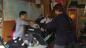 Ethan Kowatsch and Daniel Berton pack up used hockey equipment to ship to Fort Albany.
