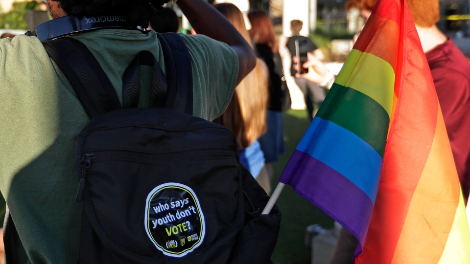 In this Wednesday, Oct. 31, 2018 photo, a student with a rainbow flag listens to speakers during a Vote for Our Lives rally at the University of Central Florida in Orlando, Fla. (AP Photo/John Raoux)