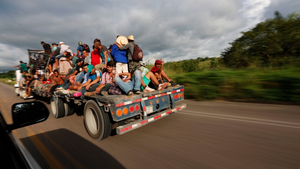 Central American migrants, part of the caravan hoping to reach the U.S. border, get a ride on a truck, in Donaji, Oaxaca state, Mexico, Friday, Nov. 2, 2018. The migrants had already made a grueling 40-mile (65-kilometer) trek from Juchitan, Oaxaca, on Thursday, after they failed to get the bus transportation they had hoped for. But hitching rides allowed them to get to Donaji early, and some headed on to a town even further north, Sayula. (AP Photo/Marco Ugarte)