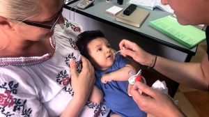 In this photo taken on Wednesday, June 6, 2018 picture, a child gets a dose of vaccine in Chitila, Romania. (AP Photo/Olimpiu Gheorghiu)