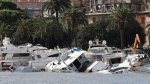 Boats are washed ashore, a day after a storm, in Rapallo, northern Italy, Tuesday, Oct. 30, 2018. At least nine people have been killed over two days in Italy as heavy rains and high winds buffet much of the country. (AP Photo/Antonio Calanni)