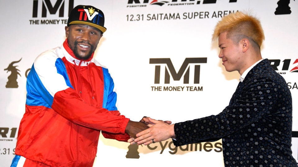 Floyd Mayweather, left, of the U.S. shakes hands with Japanese kickboxer Tenshin Nasukawa during a press conference in Tokyo, Monday, Nov. 5, 2018. (Katsuya Miyagawa/Kyodo News via AP)