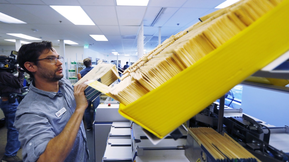 Stuart Clubb, ballot operations coordinator for the Denver Elections Division, loads ballots into a machine for tallying at elections headquarters in Denver, on Oct. 31, 2018. (David Zalubowski / AP)