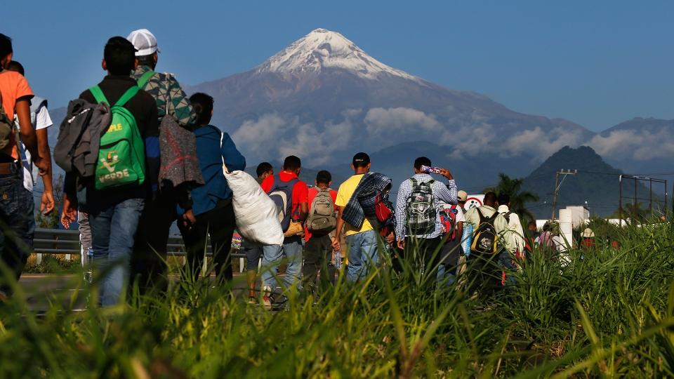 Central American migrants begin their morning trek as part of a thousands-strong caravan hoping to reach the U.S. border, as they face the Pico de Orizaba volcano upon departure from Cordoba, Veracruz state, Mexico, Monday, Nov. 5, 2018. (AP / Marco Ugarte)