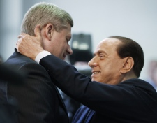 Italian Prime Minister Silvio Berlusconi welcomes Prime Minister Stephen Harper as he arrives at the G8 Summit in L'Aquila, Italy, Wednesday, July 8, 2009. (AP / Charles Dharapak)