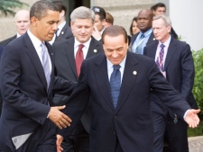 Prime Minister Stephen Harper, middle, follows as U.S. President Barack Obama, left, is offered the lead by Italy's Prime Minister Silvio Berlusconi as they arrive to the G8 leaders family photo during the G8 Summit in L'Aquila, Italy on Wednesday July 8, 2009. (Sean Kilpatrick / THE CANADIAN PRESS)