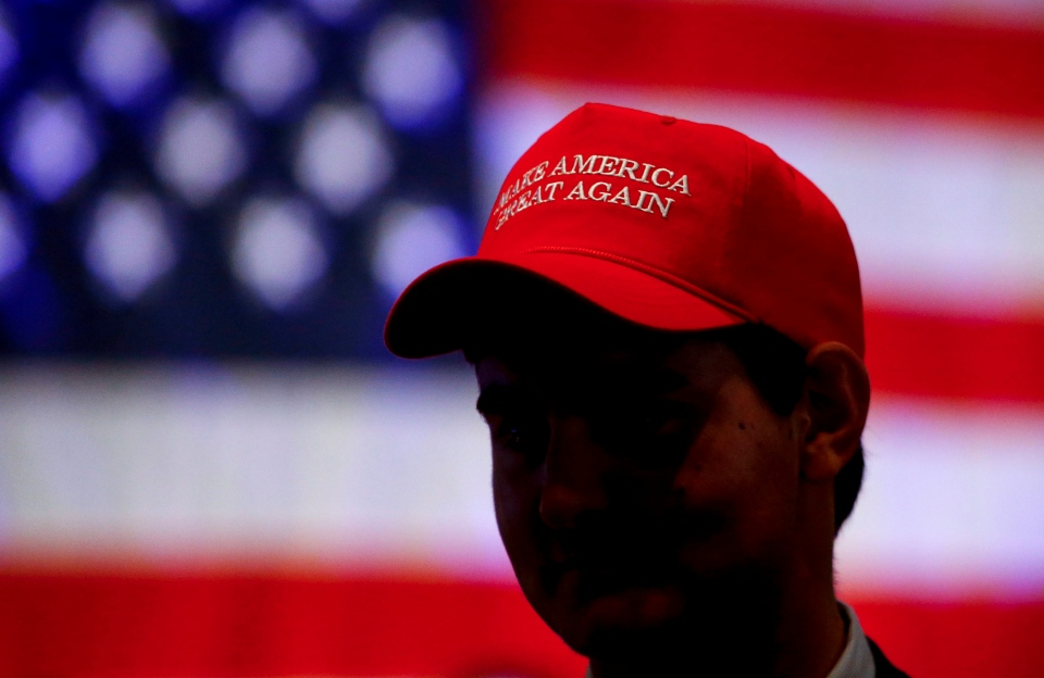 Oliver Lester, of Montgomery, wears a hat with President President Donald Trump's campaign slogan as he watches results come in for Gov. Kay Ivey at a watch party, Tuesday, Nov. 6, 2018, in Montgomery, Ala. (AP Photo/Butch Dill)