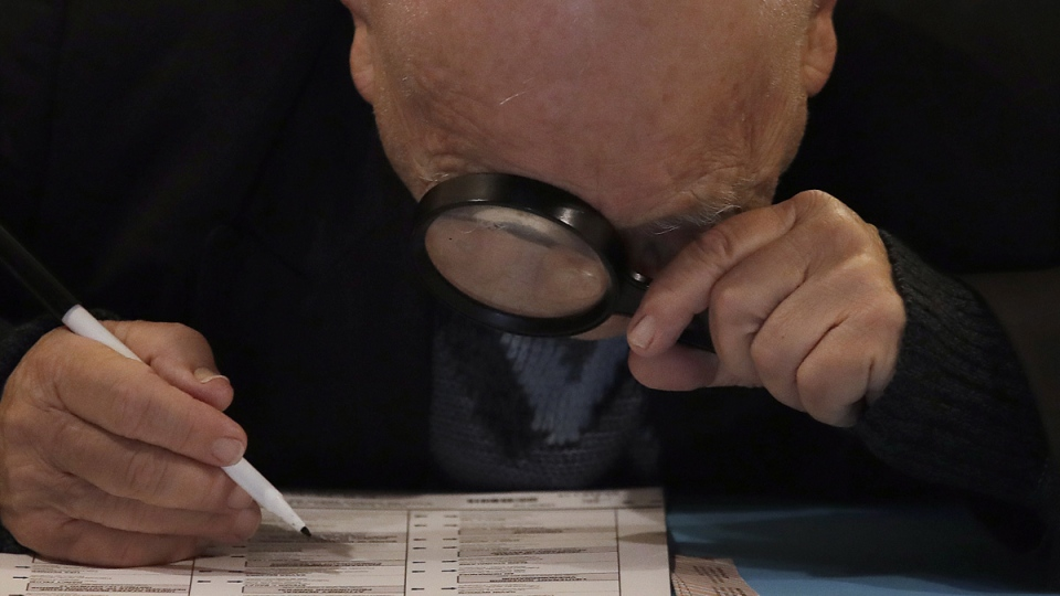 Yuriy Glukhoy looks through a magnifying glass at his ballot while voting at San Francisco Columbarium & Funeral Home in San Francisco, on Nov. 6, 2018. (Jeff Chiu / AP)