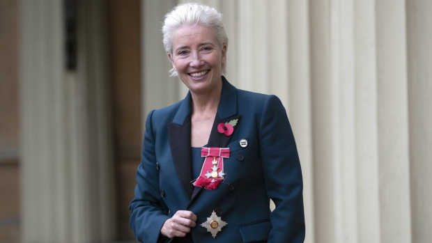 Emma Thompson stands outside Buckingham Palace