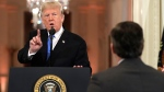 U.S. President Donald Trump speaks as CNN's Jim Acosta, standing at right, listens, during a news conference in the East Room of the White House, Wednesday, Nov. 7, 2018, in Washington. (AP Photo/Evan Vucci)