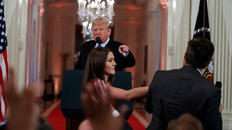 U.S. President Donald Trump watches as a White House aide reaches to take away a microphone from CNN journalist Jim Acosta during a news conference in the East Room of the White House, Wednesday, Nov. 7, 2018, in Washington. (AP Photo/Evan Vucci)