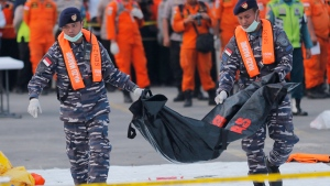 In this Thursday, Nov. 1, 2018, file photo, navy personnel carry the remains of a victim of Lion Air jet that crashed into the sea at the Tanjung Priok Port in Jakarta, Indonesia. (AP Photo/Tatan Syuflana, File)