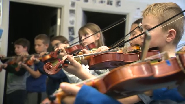 Students at Cayley School play the fiddle during the November 7 appearance by the members of the Rolston String Quartet