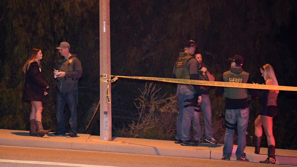 Sheriff's deputies speak to a potential witnesses as they stand near the scene Thursday, Nov. 8, 2018, in Thousand Oaks, Calif. (AP Photo/Mark J. Terrill)