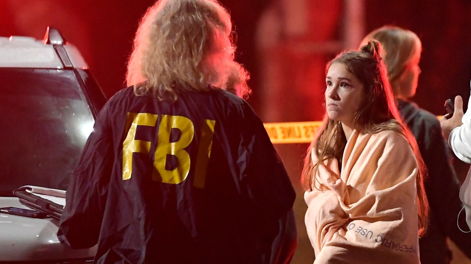 An FBI agent talks to a potential witness as they stand near the scene Thursday, Nov. 8, 2018, in Thousand Oaks, Calif. (AP Photo/Mark J. Terrill)