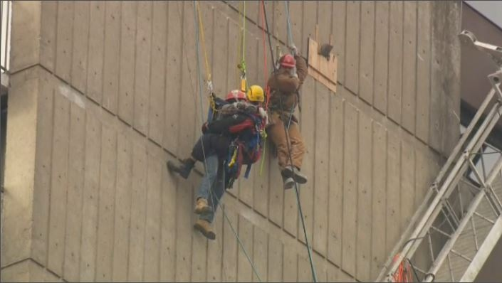 The two workers were left suspended by only wires and harnesses alongside the 23-storey building in Cote-St-Luc when their scaffold collapsed. (CTV Montreal)
