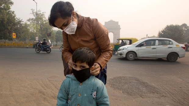 An Indian mother puts a mask to her son