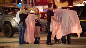 People comfort each other as they stand near the scene Thursday, Nov. 8, 2018, in Thousand Oaks, Calif. where a gunman opened fire Wednesday inside a country dance bar crowded with hundreds of people on 'college night,' wounding 11 people including a deputy who rushed to the scene. Ventura County sheriff's spokesman says gunman is dead inside the bar. (AP / Mark J. Terrill)