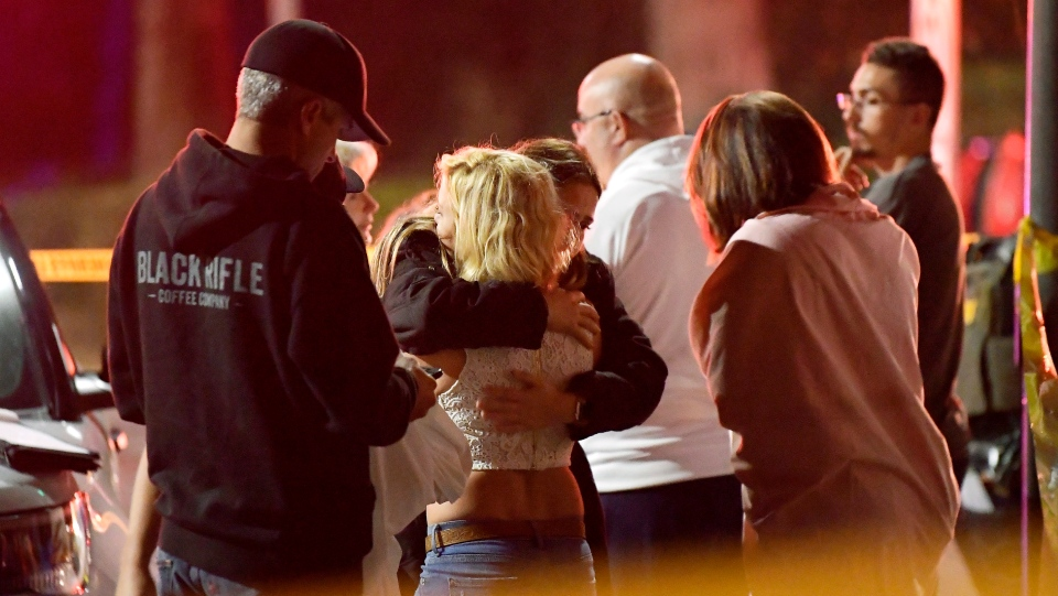 People comfort each other as they stand near the scene Thursday, Nov. 8, 2018, in Thousand Oaks, Calif. (AP Photo/Mark J. Terrill)