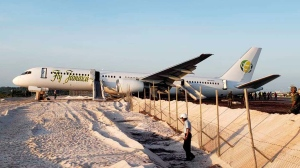 A Fly Jamaica Boeing 757-200 aircraft, which overshot the runway, sits at the northeastern takeoff end of the runway at the Cheddi Jagan International Airport, in Georgetown, Guyana, Friday, Nov. 9, 2018. An airline spokesman said the plane, which was on its way to Toronto, reported a hydraulic failure emergency shortly after taking off and returned after less than 20 minutes. Several people were injured. (AP Photo/Adrian Narine)