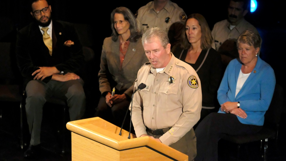 Ventura County Sheriff Geoff Dean, front, speaks during a candlelight vigil in Thousand Oaks, Calif., Thursday, Nov. 8, 2018. (AP Photo/Ringo H.W. Chiu)