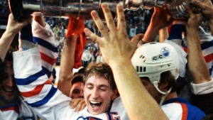 Edmonton Oiler captain Wayne Gretzky holds up the Stanley Cup while being mobbed by well-wishers after the Oilers won the cup in the fifth game against the Phildaelphia Flyers in Edmonton on Thursday night, May 30, 1985. Oiler centre Mike Krushelnyski is next to Gretzky. (CP PHOTO.Dave Buston)