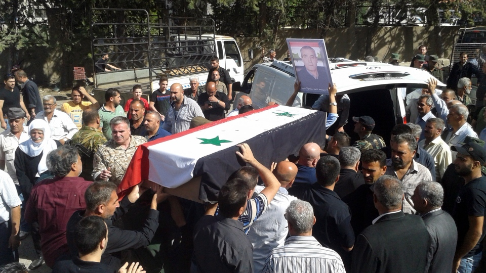 In this Thursday, July 26, 2018, file photo, released by the Syrian official news agency SANA, mourners carry a coffin of more than 200 people who were killed a day earlier by a series of suicide bombings launched by the Islamic State's fighters on the eastern and northern countryside of the southern province of Sweida during a mass funeral. (SANA via AP, File)