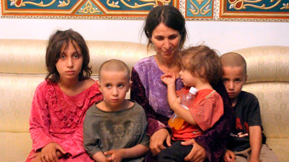 In this Thursday, July 26, 2018, file photo, released by the Syrian official news agency SANA, Abeer Shalgheen and her four children after being freed by the Islamic State group that kidnapped them on July 25 during a raid by the extremists on the southern province of Sweida. (SANA via AP, File)