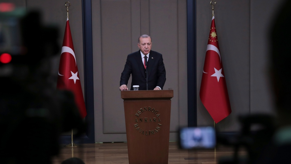 Turkey's President Recep Tayyip Erdogan talks to members of the media at the airport in Ankara, Turkey before departing to France, Saturday, Nov. 10, 2018. (Presidential Press Service via AP, Pool)