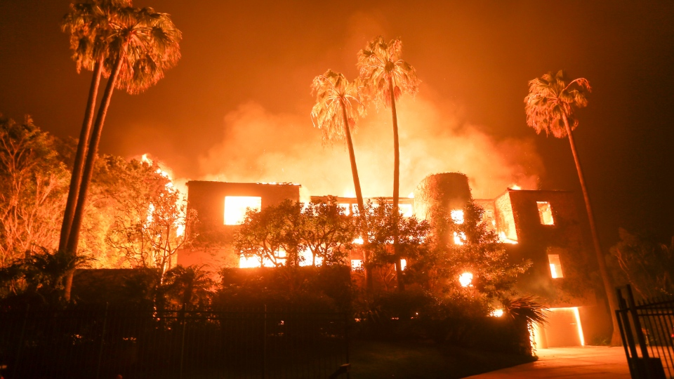 A firefighter walks by the a burning home in Malibu, Calif., Friday, Nov. 9, 2018.  (AP Photo/Ringo H.W. Chiu)