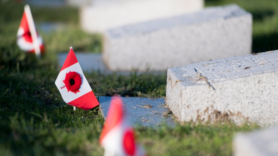 Poppies and Canadian flags are seen at the graves of soldiers at Mountain View Cemetery in Vancouver, Saturday, Nov. 10, 2018. THE CANADIAN PRESS/Jonathan Hayward
