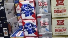 In this photo taken on Thursday, Nov. 8, 2018, cases of Pabst Blue Ribbon and Coors Light are stacked next to each other in a Milwaukee liquor store. (AP Photo/Ivan Moreno)