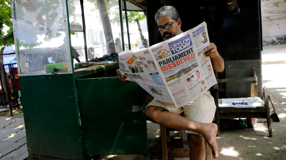 A Sri Lankan man reads a newspaper reporting about the dissolution of parliament in Colombo, Sri Lanka, Saturday, Nov. 10, 2018. (AP Photo/Eranga Jayawardena)