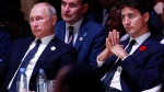 Russian President Vladimir Putin, left, and Canadian Prime Minister Justin Trudeau attend the opening session of the Paris Peace Forum as part of the commemoration ceremony for Armistice Day, in Paris, Sunday, Nov. 11, 2018. (Gonzalo Fuentes, Pool via AP)