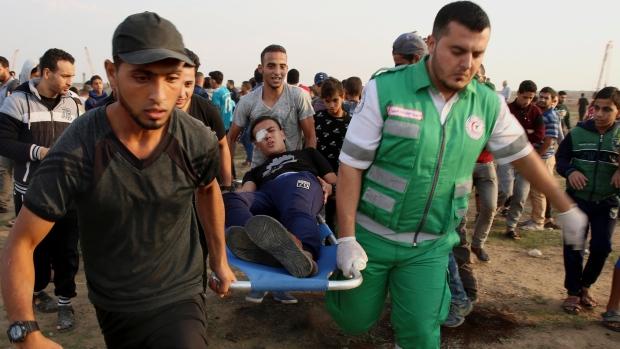 Medics carry an injured man in Gaza Strip
