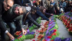 People place their poppies on wreaths at the Victory Square Cenotaph after a Remembrance Day ceremony in Vancouver, on Sunday November 11, 2018. THE CANADIAN PRESS/Darryl Dyck