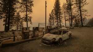 As the Camp Fire burns nearby, a scorched car rests by gas pumps near Pulga, Calif., on Sunday, Nov. 11, 2018. (AP Photo/Noah Berger)
