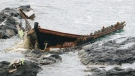 A wooden boat is left after being washed ashore in Tsuruoka, Yamagata prefecture, northern Japan, on Dec. 4, 2017. (Kyodo News via AP)